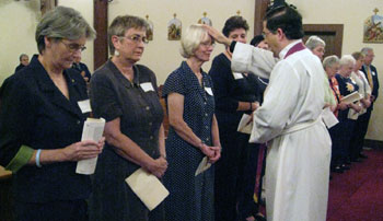 Fr. Pavone blesses Lay Missionary, Jane Witzman and other promise makers.