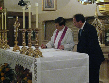 Fr. Pavone signs profession documents as Jim Pinto looks on.