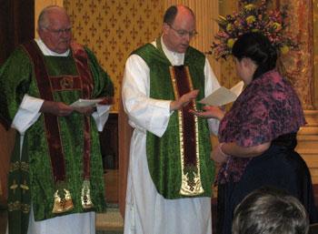 Msgr. Farmer prays over Beth and blesses her MEV pin.