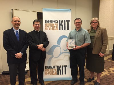 From left to right, Dr. Delgado, Fr. Frank, Dr. Matt Harrison and Dr. Mary Davenport. Dr. Harrison is holding the RU-486