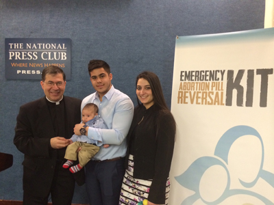 <p>Fr. Frank Pavone, national director of Priests for Life, with Chris Caicedo, Andrea Minichini and their son, Gabriel Caicedo, following a news conference at the National Press Club in Washington Feb. 23 to call attention to a protocol to reverse RU-486 medical abortions. 