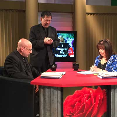 Fr. Frank, Fr. Stephen and Janet pray on the set before taping.