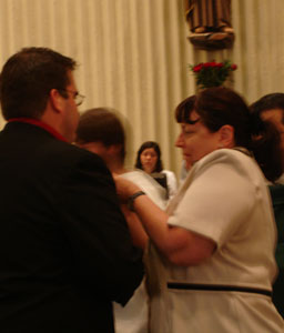 Janet Morana, Associate Director of Priests for Life, helps Justin with his Missisonary of the Gospel of Life pin