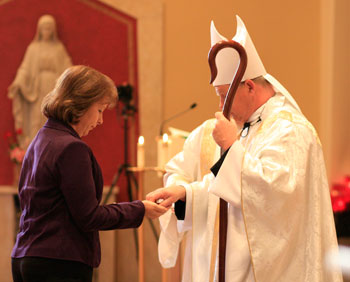 Sandi Davidson, Director of Pregnancy Help Services for Catholic Charities of East Tennessee, receiving her MEV pin from Bishop Richard F. Stika
