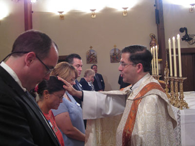 Fr. Frank praying with Helga Burns and newly professed Missionaries of the Gospel of Life-MEV.