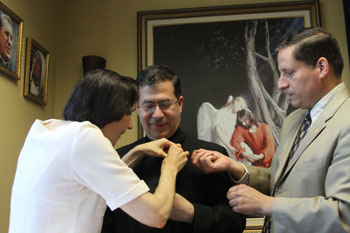 Fr. Frank Pavone, center, national director of Priests for Life, is made an honorary member of the St. Gianna Physician's Guild, which encourages doctors to be actively pro-life. Dr. Gianna Molla of Milan pins Father Pavone, with the help of Thomas McKenna, founder of the guild