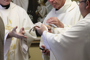 The Priests touch St. Gianna's gloves