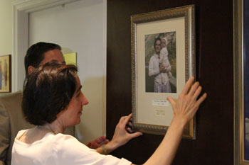 Dr. Molla hangs the picture of St. Gianna and her daughter Mariolina