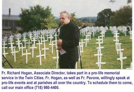 Photo: Fr. Hogan leads memorial service at graveyard. (27850 bytes)